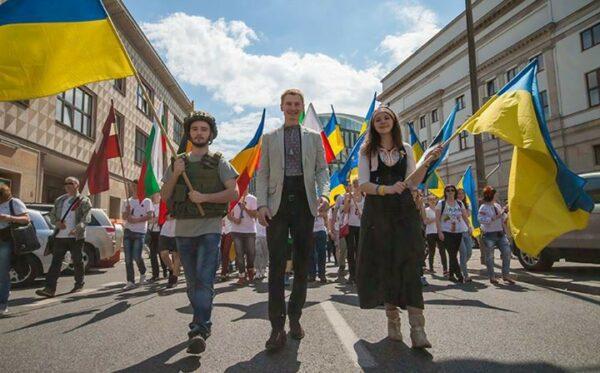 Желто-голубые флаги в передней части колонны. Фундация «Открытый Диалог» приняла участие в Параде Шумана