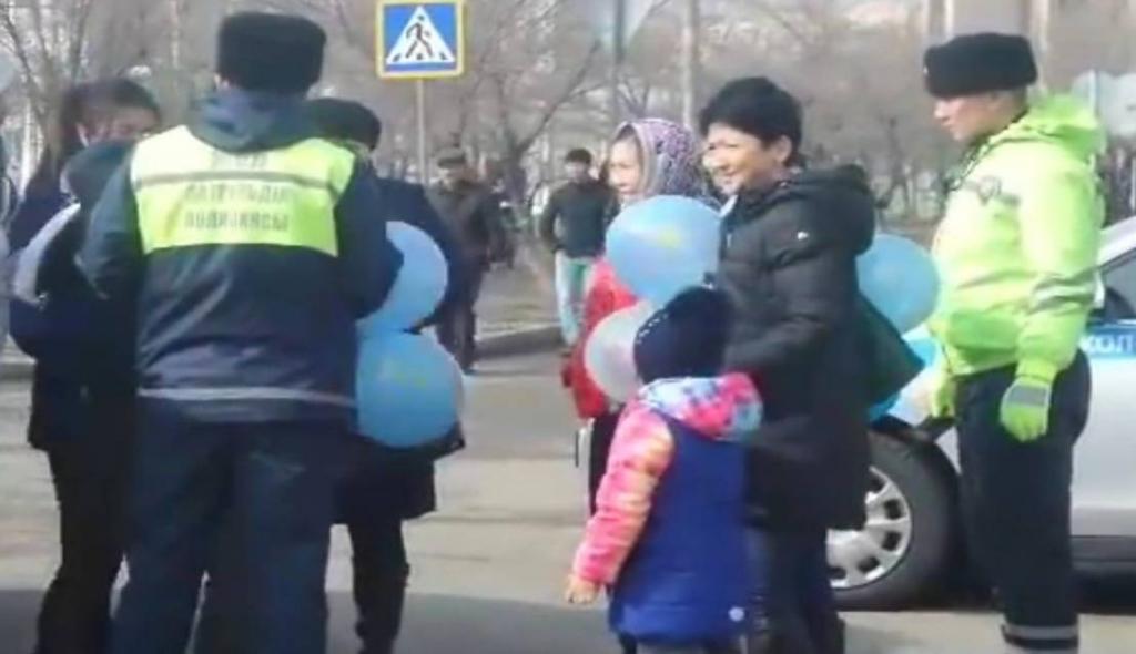 Полицейские останавливают семьи, которые гуляют c синими воздушными шариками. Источник: канал OSCEKZ на Youtube