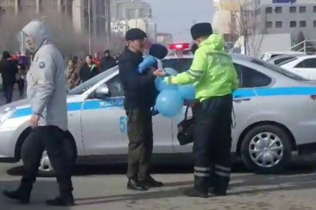 Полицейские проверяют документы людей, которые гуляют c синими воздушными шариками. Источник: канал OSCEKZ на Youtube